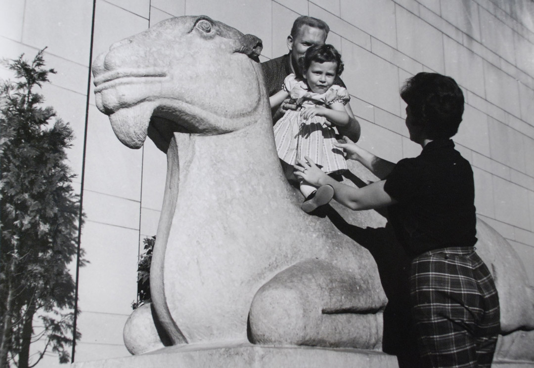 Black and white photograph of two parents and a child atop the iconic Asian Art Museum camel