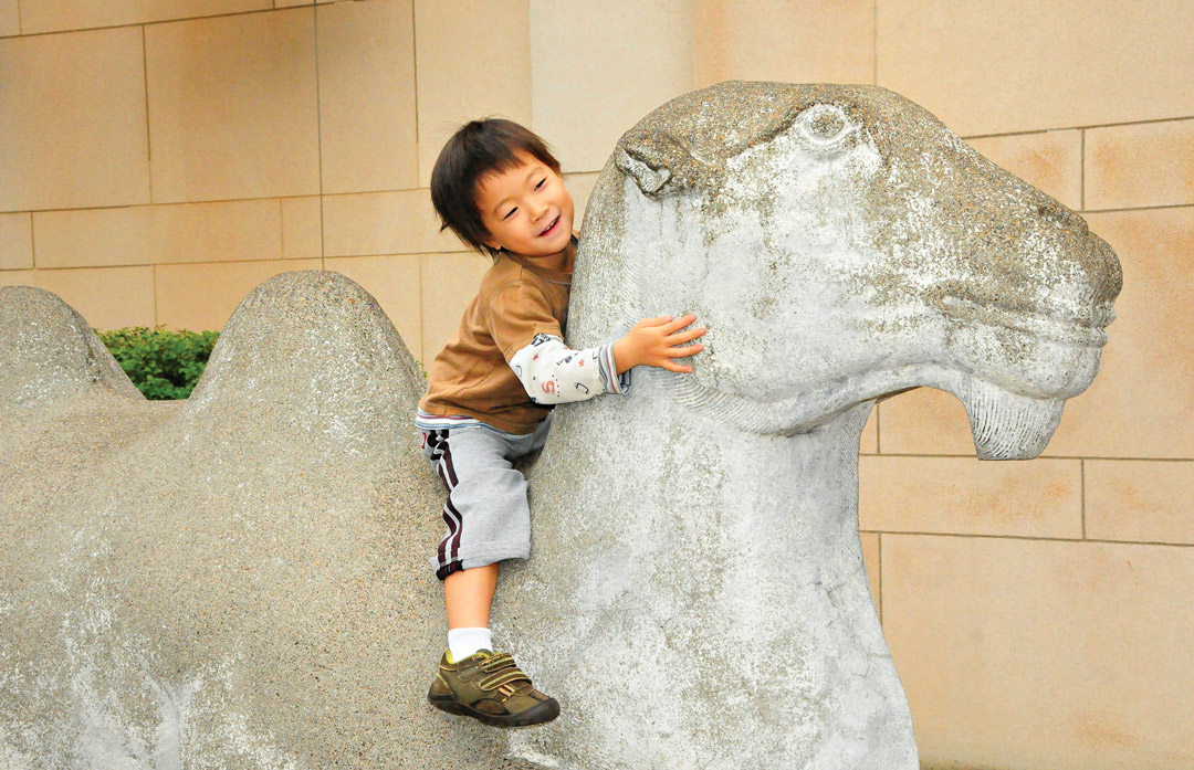 Young child sits upon an iconic Asian Art Museum camel