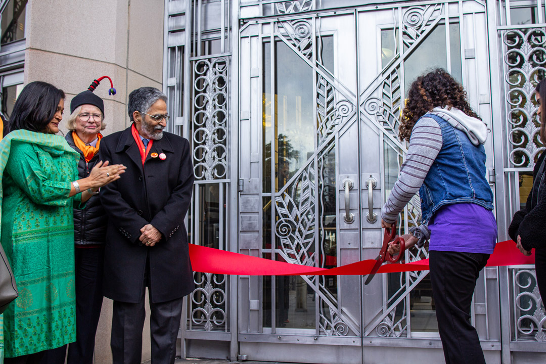 A person cutting the ribbon at the doors of the Asian Art Museum while onlookers applaud.